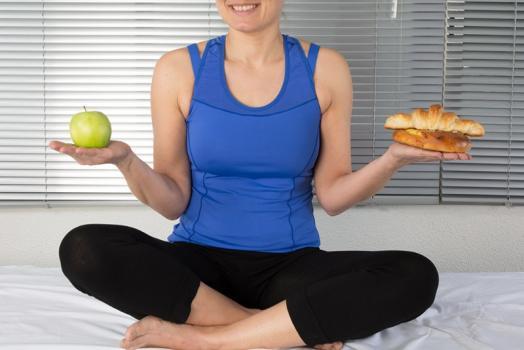 Femme tenant une pomme dans une main, et un croissant dans l'autre